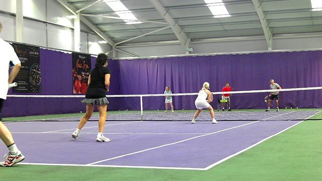 People playing tennis in an indoor facility