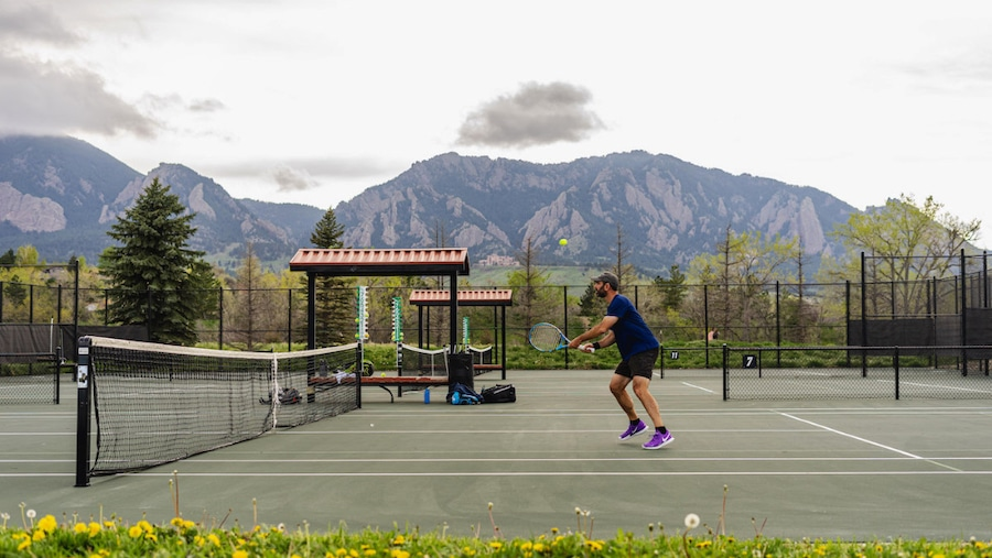 Net player against backdrop of Flatirons